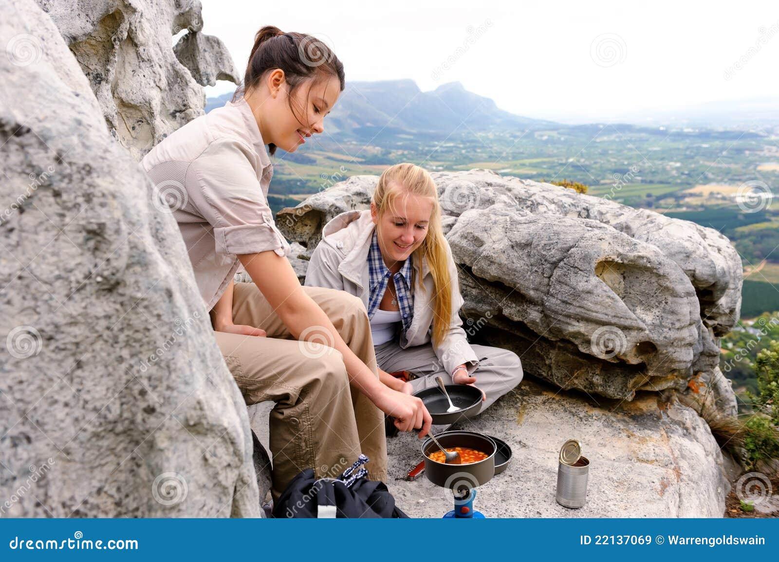 Os caminhantes da montanha cozinham o alimento