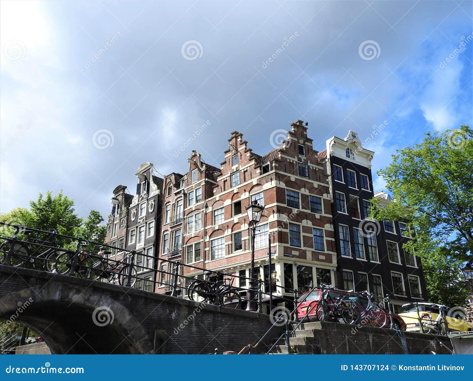 Os canais de Amsterdão, os Países Baixos, dia de verão claro