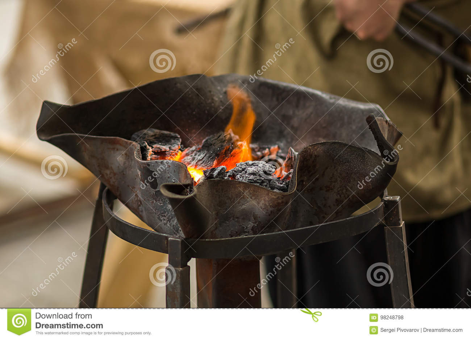 Os carvões alaranjados do fogo para o chifre da forja em um metal a céu aberto rolam