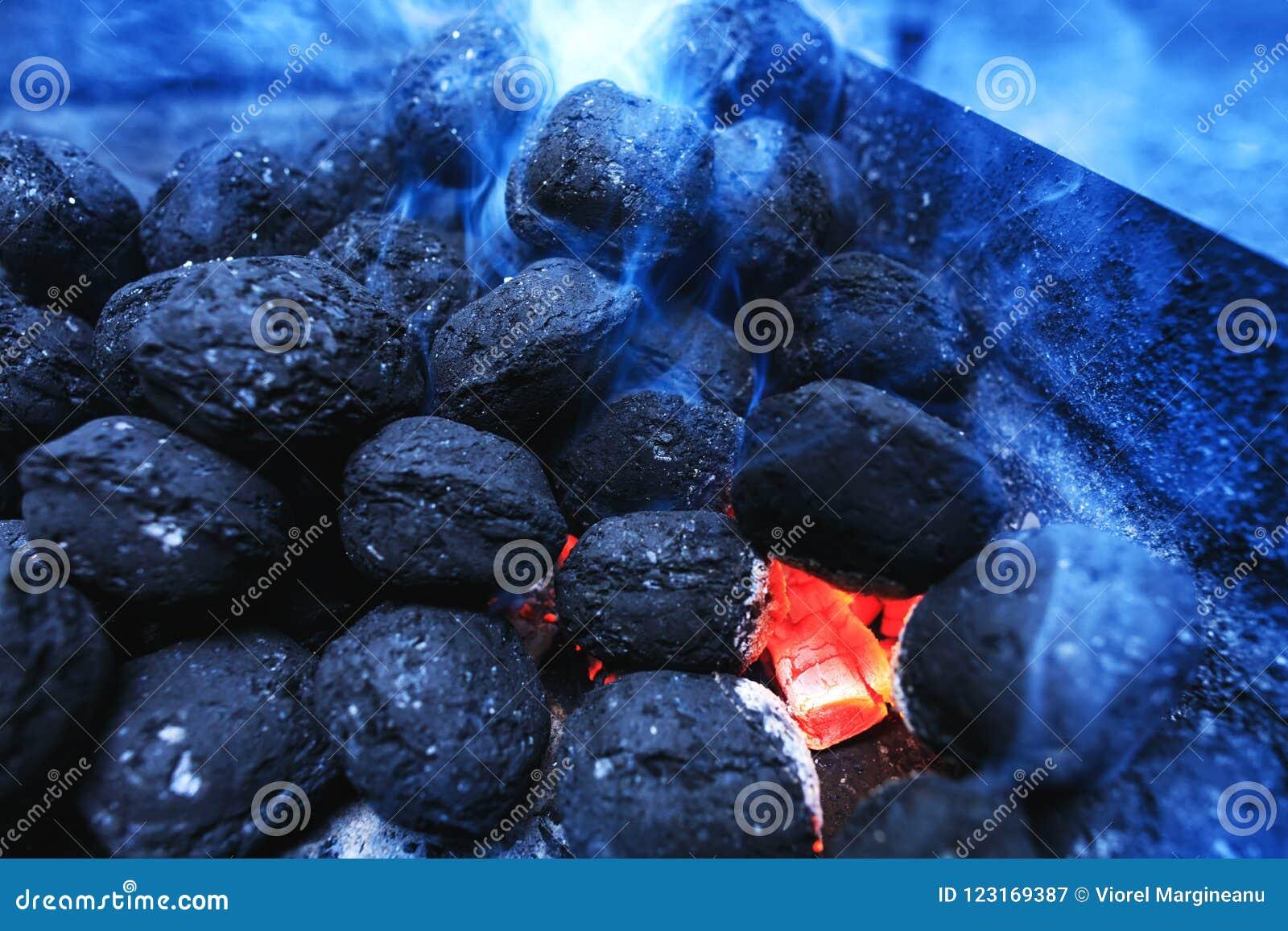 Os carvões amassados flamejantes quentes do carvão vegetal que incandescem no assado grelham o pi