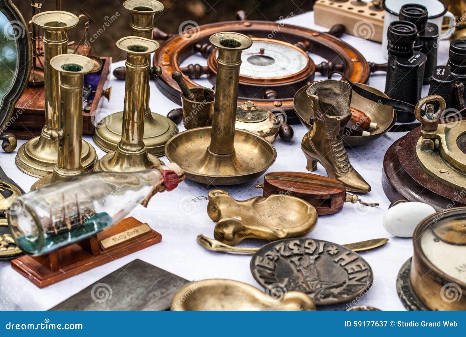 Os castiçais de bronze da segunda mão no negociante antigo mostram