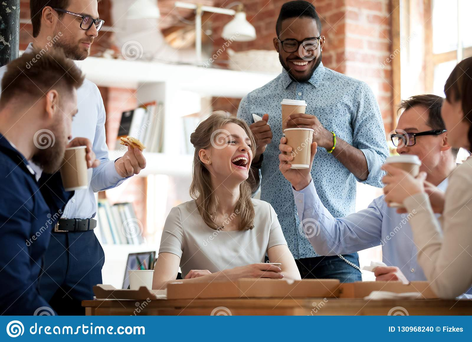 Os colegas diversos felizes comemoram durante a pausa para o almoço no escritório