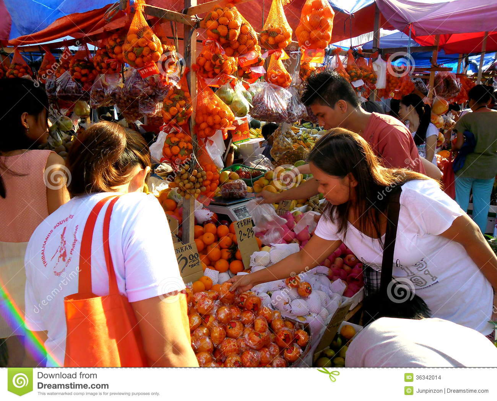 Os consumidores compram de um vendedor do fruto em um mercado em Cainta, Rizal, Filipinas, Ásia