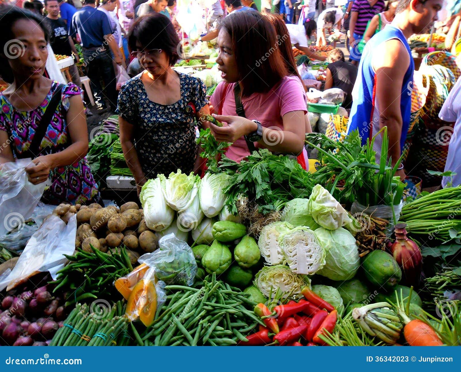Os consumidores compram de um vendedor vegetal em um mercado em Cainta, Rizal, Filipinas, Ásia