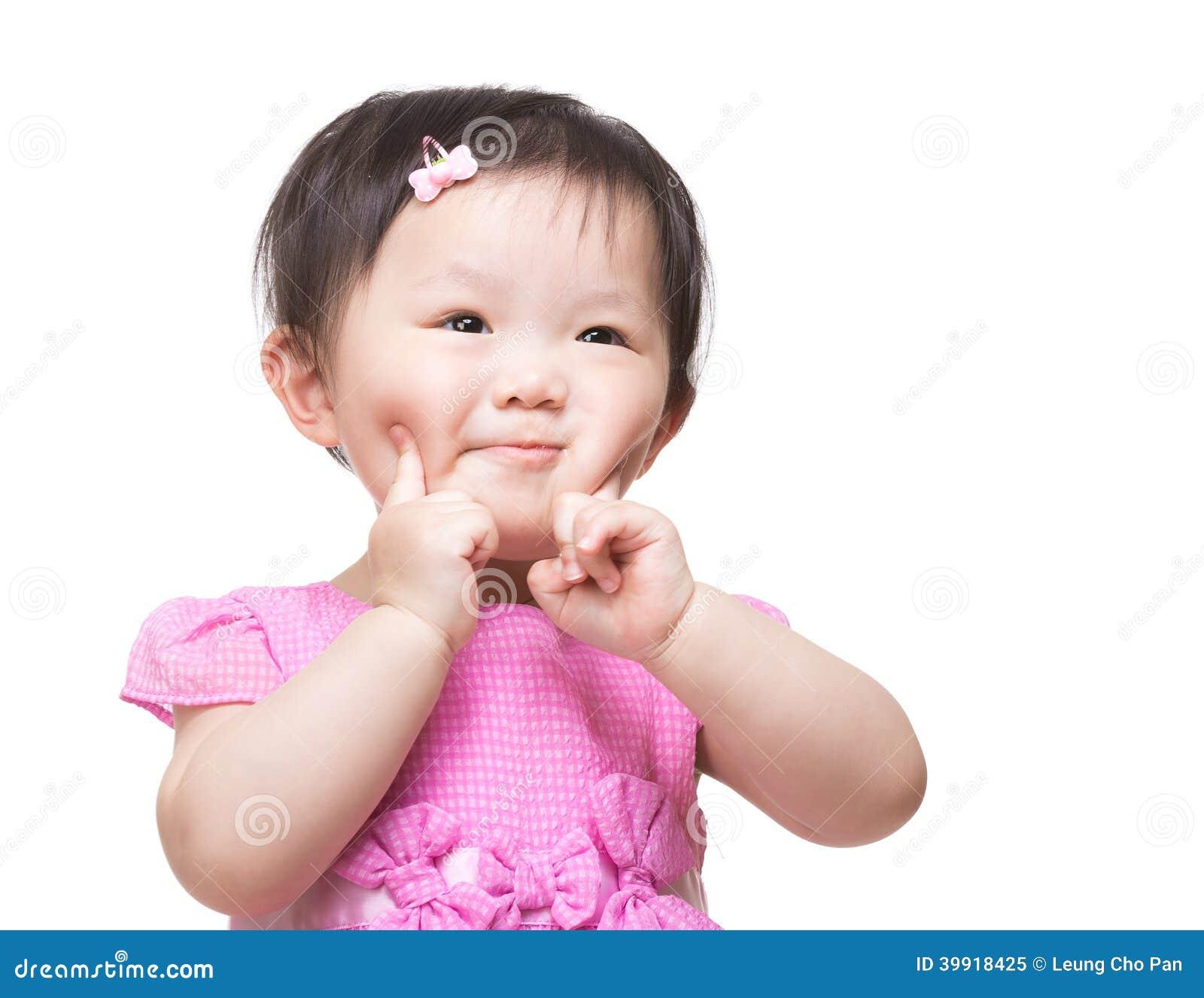 Os dedos asiáticos do bebê dois tocam em sua cara