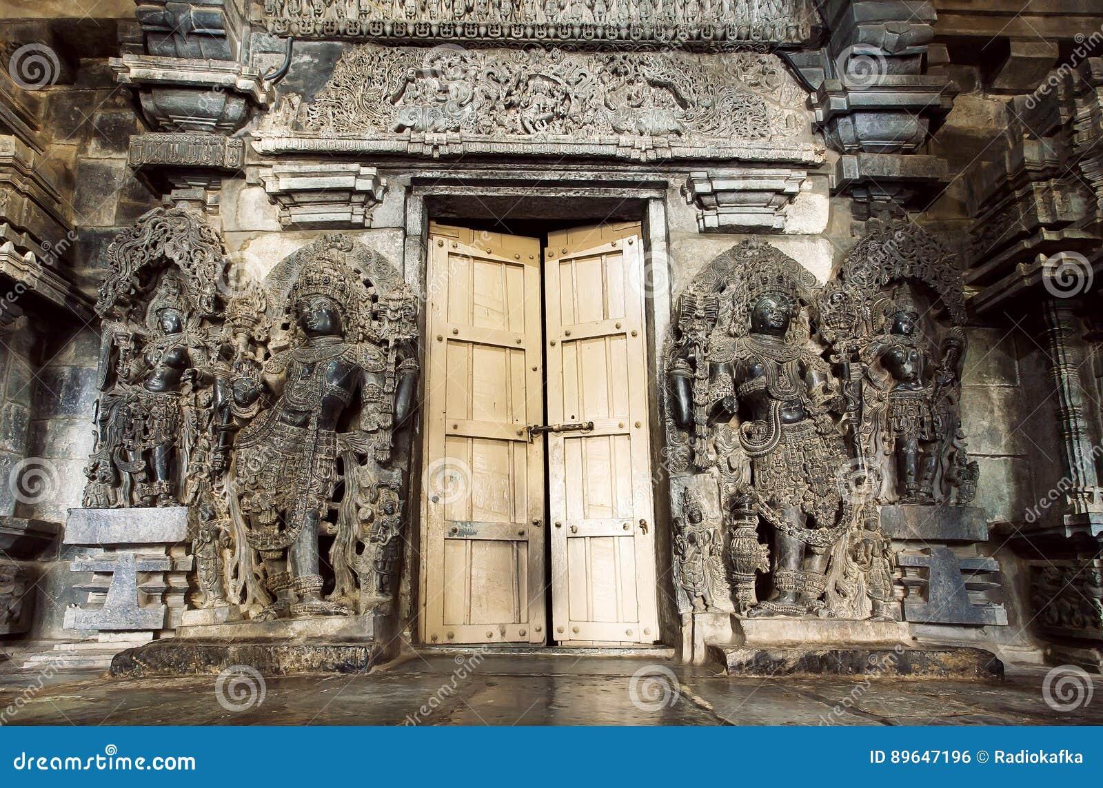 Os deuses hindu na porta de entrada ao estilo tradicional apedrejam o templo de Hoysaleswara, estrutura do século XII, Índia