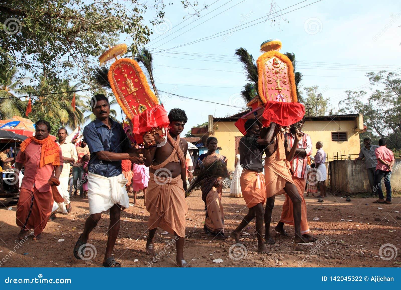 Os devotos guardam o arco decorado e a dança na agitação durante o festival de Thaipuyam