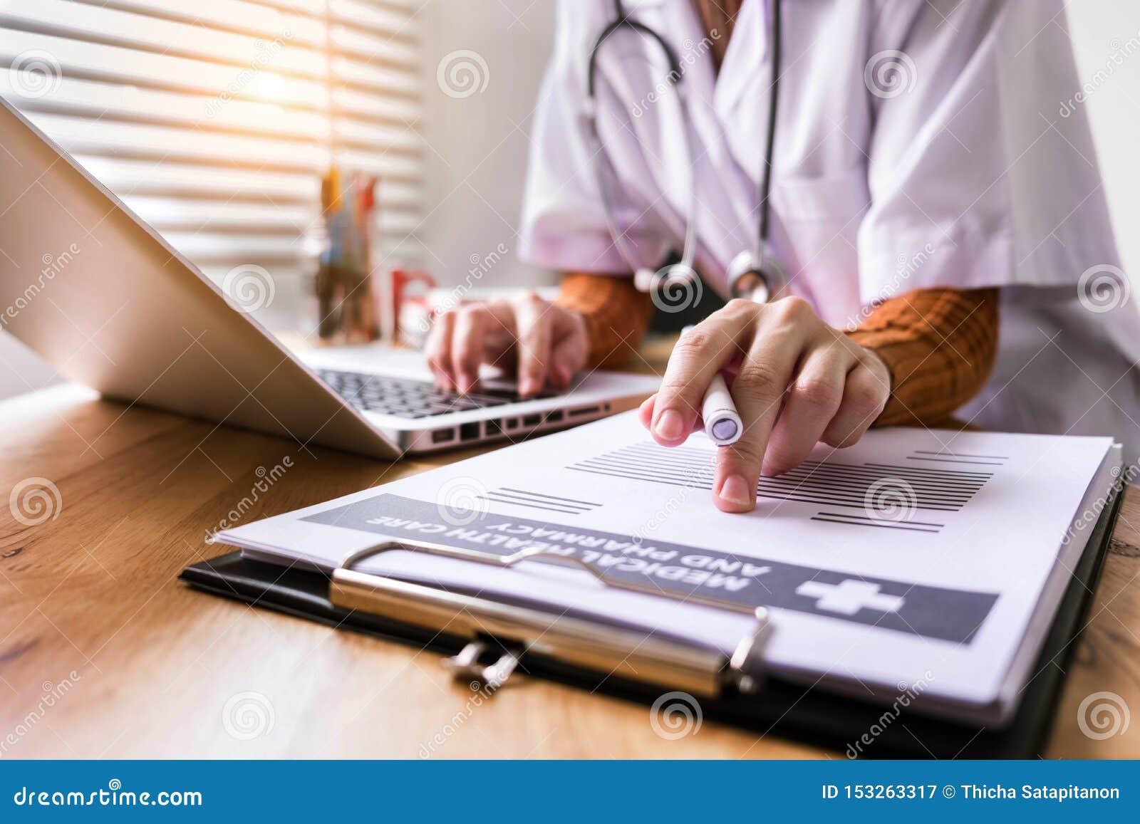 Os doutores das mulheres sentam-se para escrever relatórios pacientes no escritório