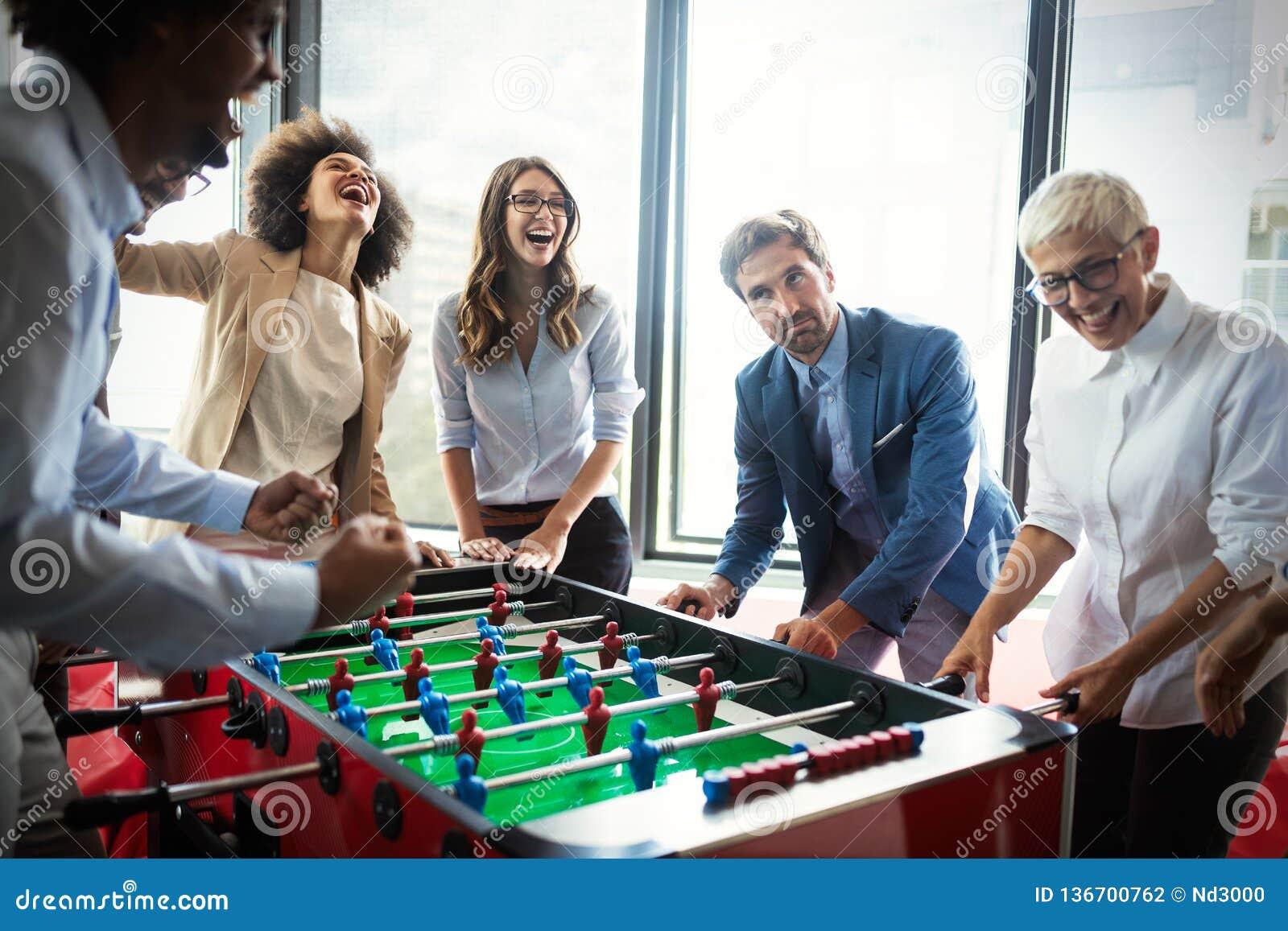 Os empregados diversos entusiasmados que apreciam a atividade engraçada na ruptura de trabalho, trabalhadores amigáveis criativos