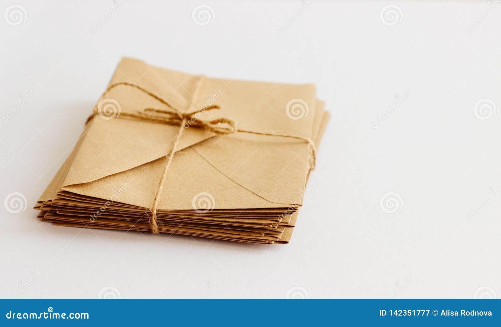 Os envelopes de Kraft encontram-se em um fundo claro amarrado com guita