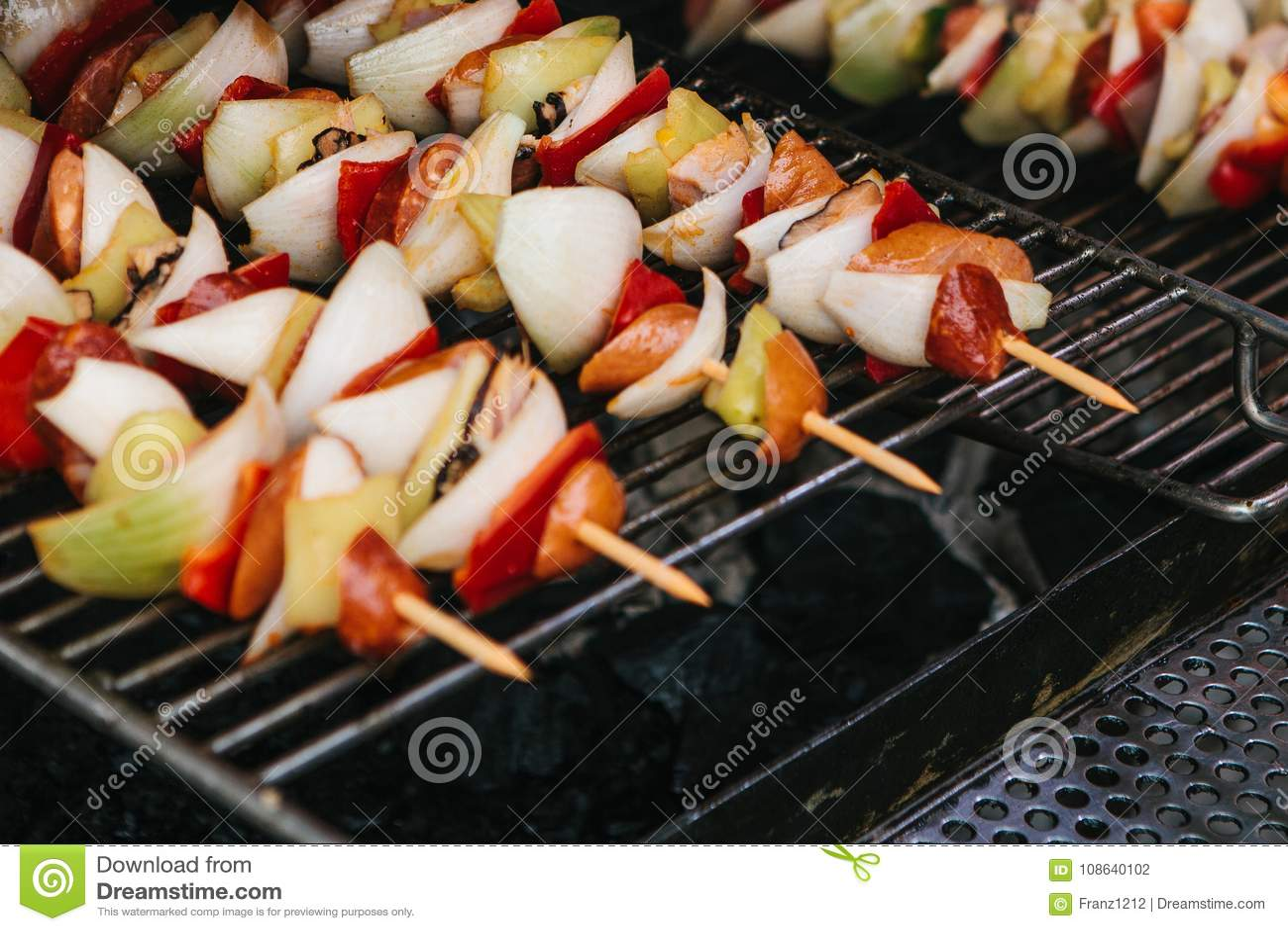 Os espetos com partes de salsichas, cebolas, pimentas são cozinhados em uma grelha em carvões Resto e comer fora
