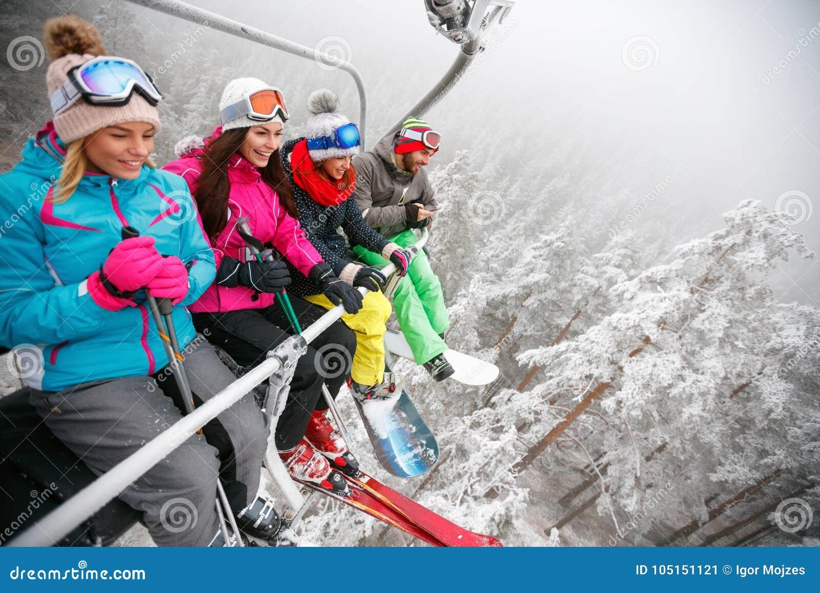 Os esquiadores dos amigos no elevador de esqui montam acima na inclinação do esqui no dia nevado