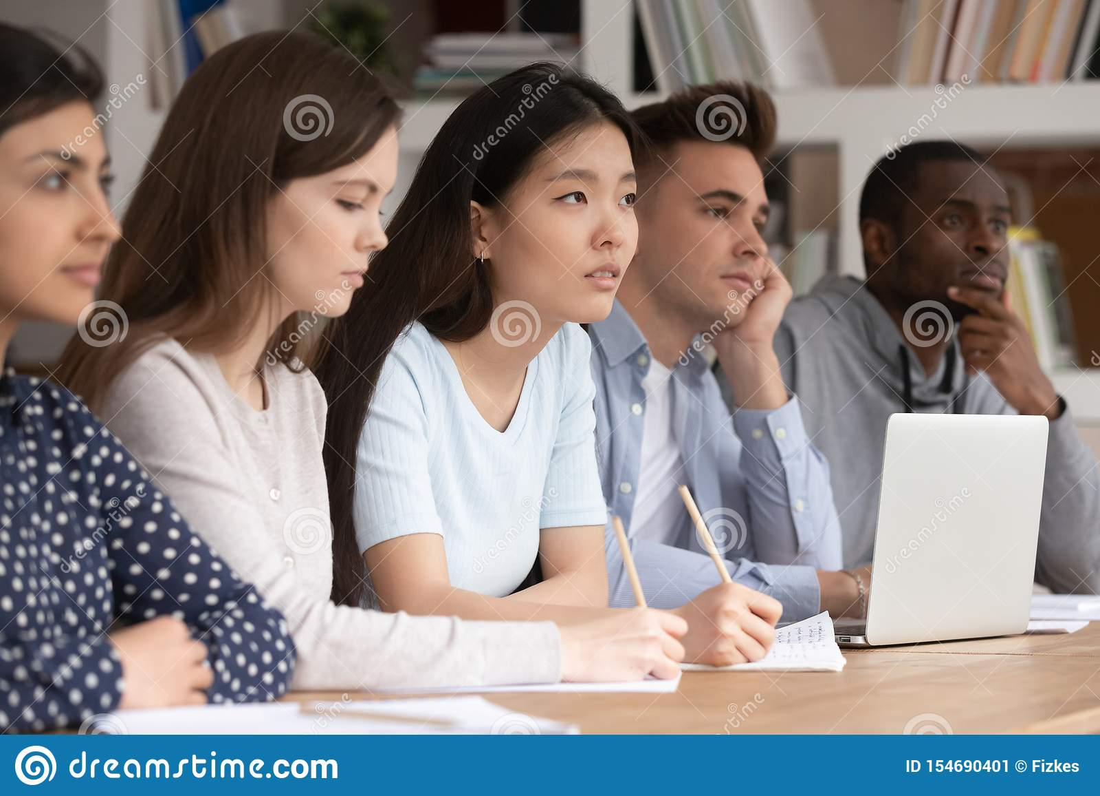 Os estudantes diversos concentrados escutam a leitura do professor