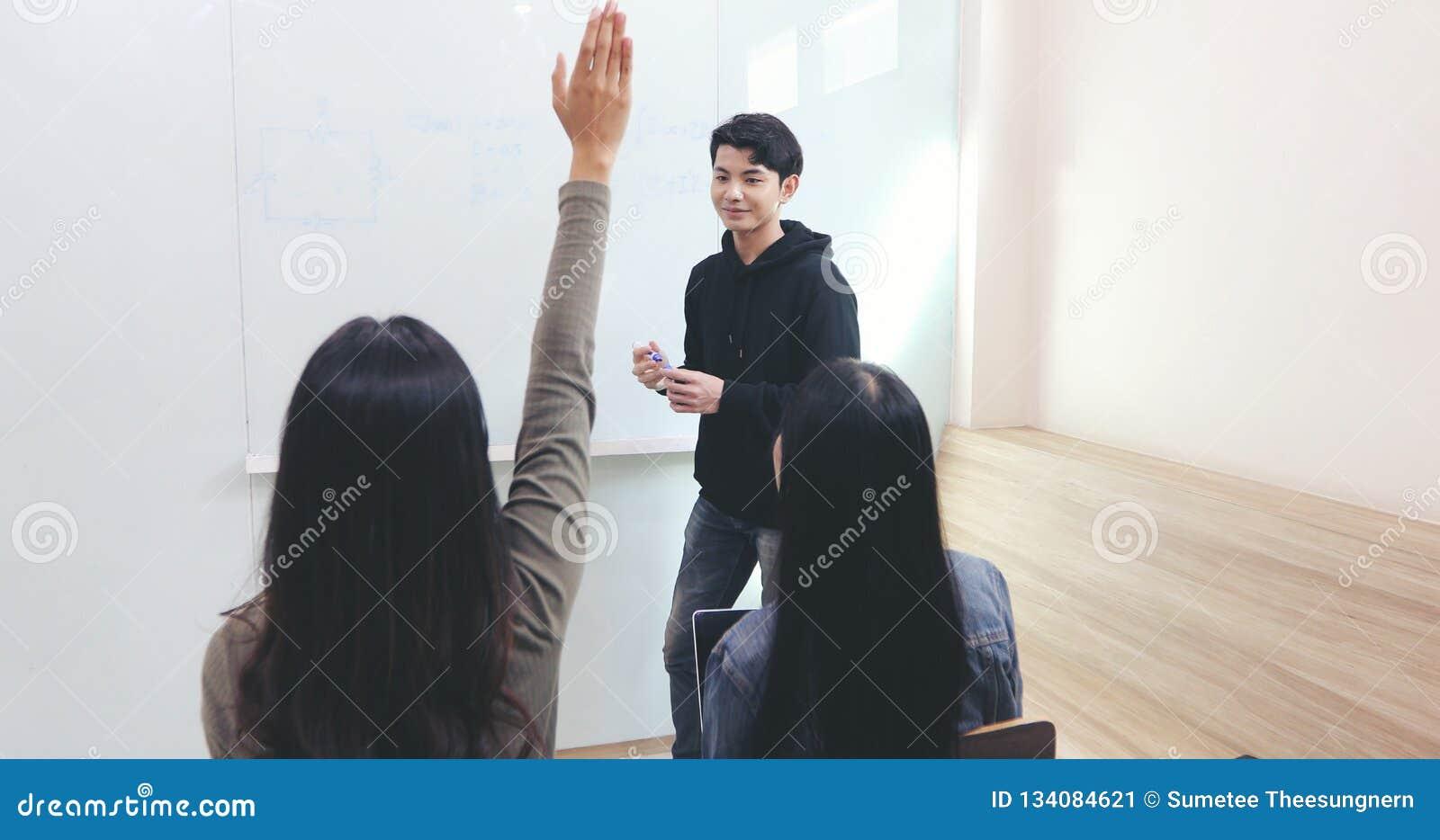 Os estudantes do grupo levantam suas mãos para pedir a um amigo perguntas ensinar no whiteboard na sala de aula