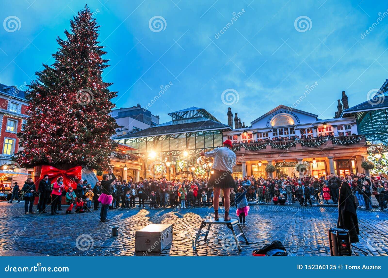 Os executores e o Natal da rua treen em Covent Garden, Londres, Inglaterra, Reino Unido, Europa