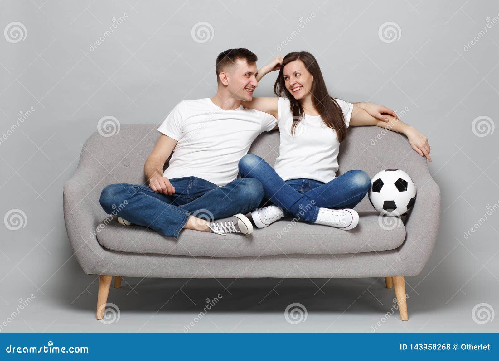 Os fan de futebol alegres do homem da mulher dos pares no elogio branco do t-shirt acima da equipe favorita do apoio com a bola d