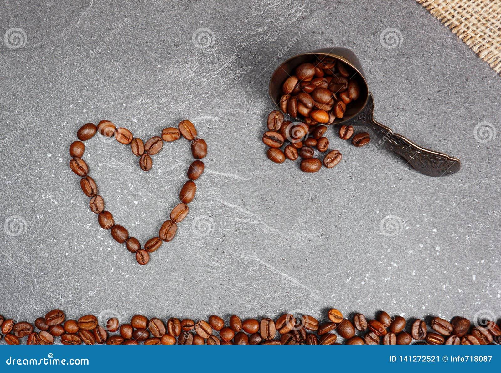 Os feijões de café afrouxam o comércio justo com colher e o coração no fundo do worktop da cozinha