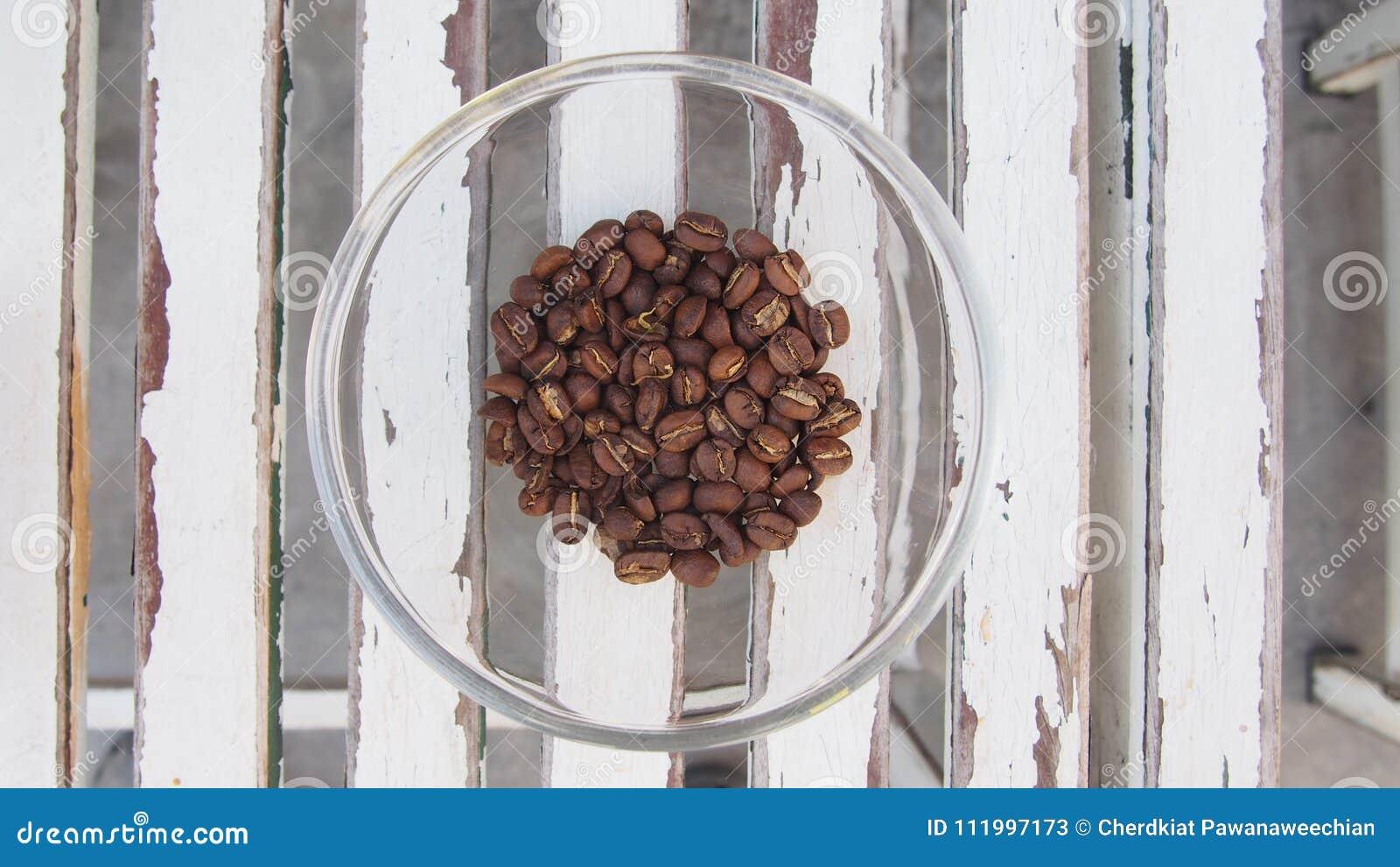 Os feijões de café empilham no montão de vidro na tabela de madeira, vista superior