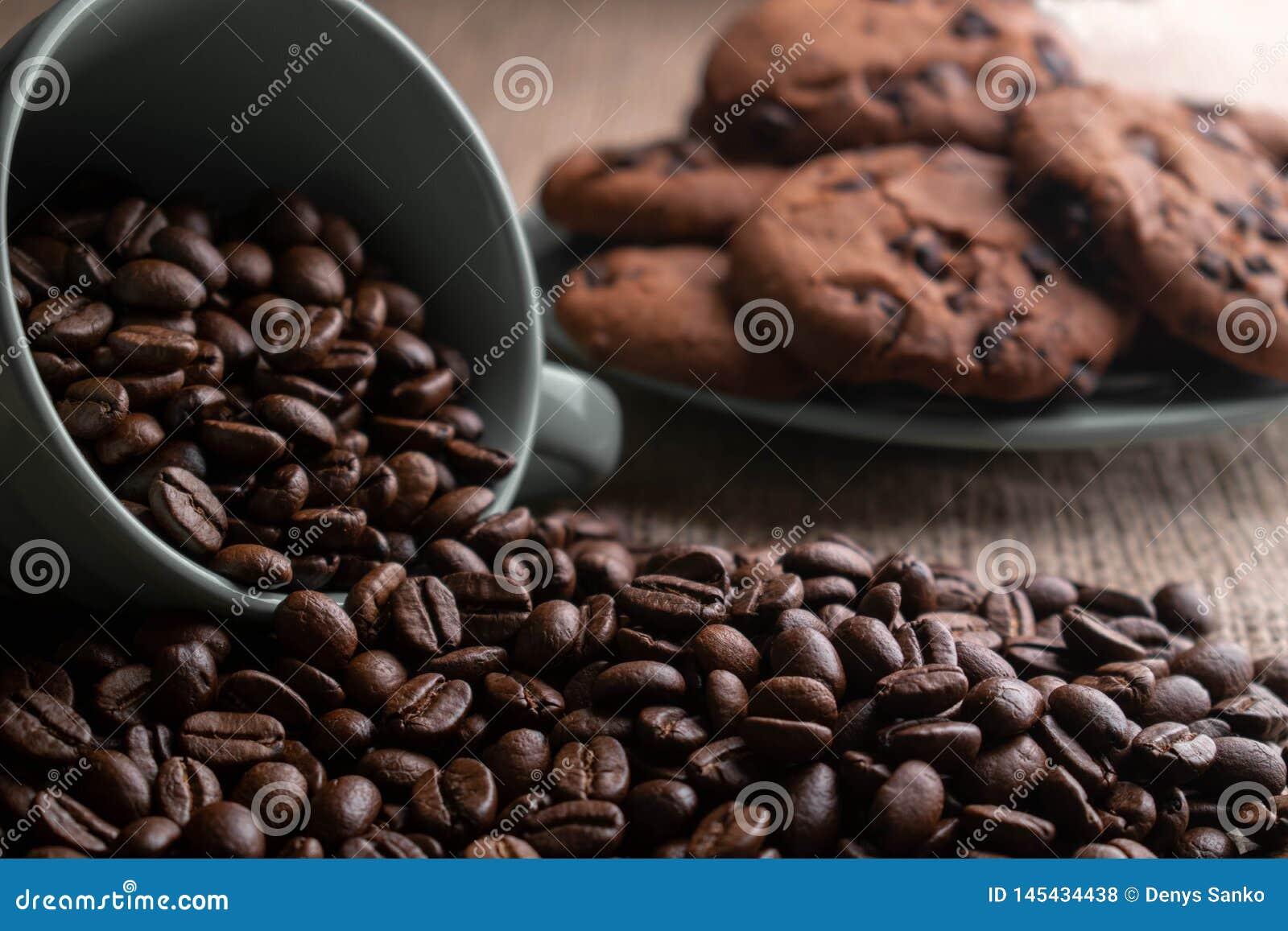 Os feij?es de caf? desintegraram-se com um copo, no fundo uma placa das cookies