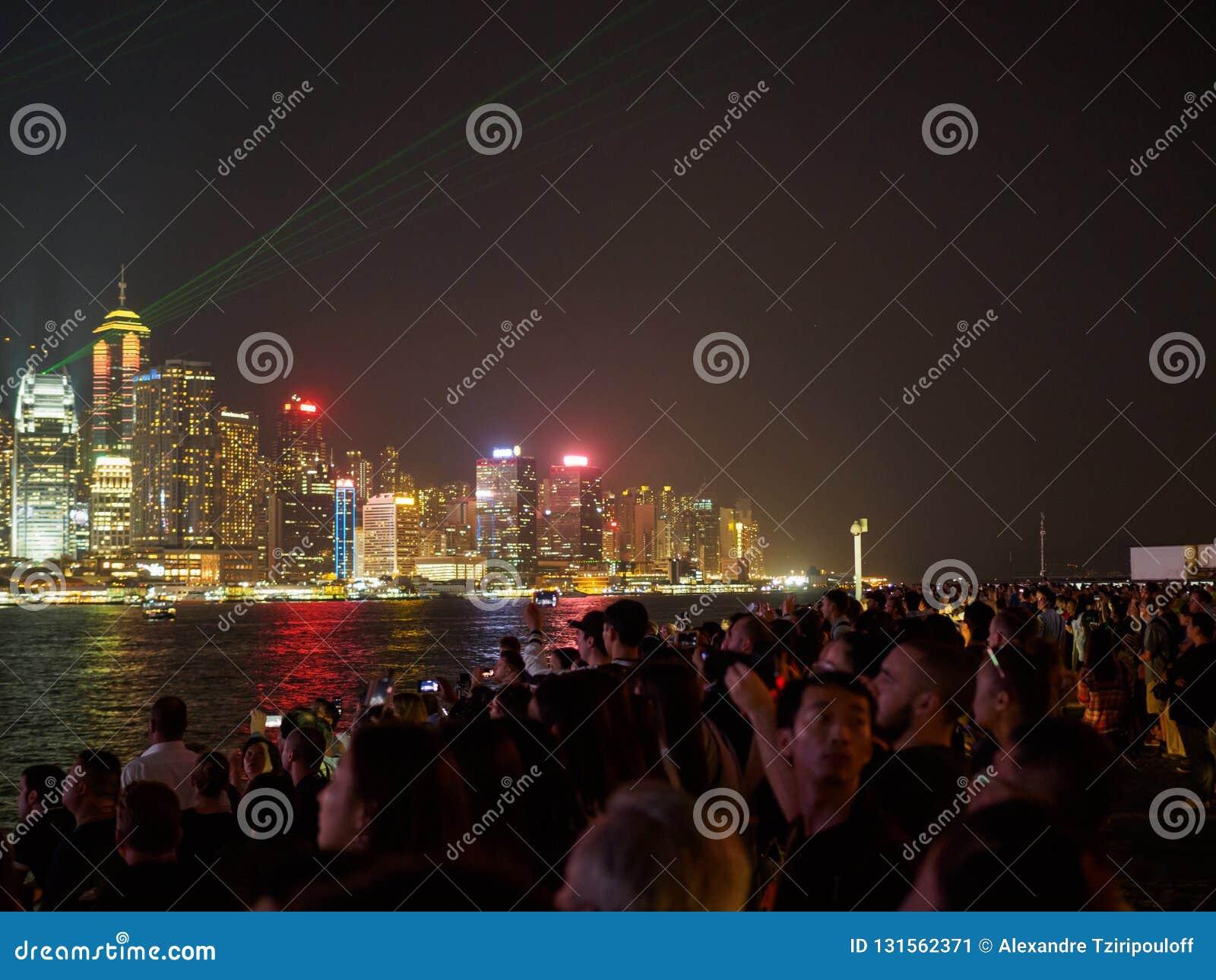Os grandes grupos de pessoas recolhem no cais de Kownloon para admirar a sinfonia do espetáculo A