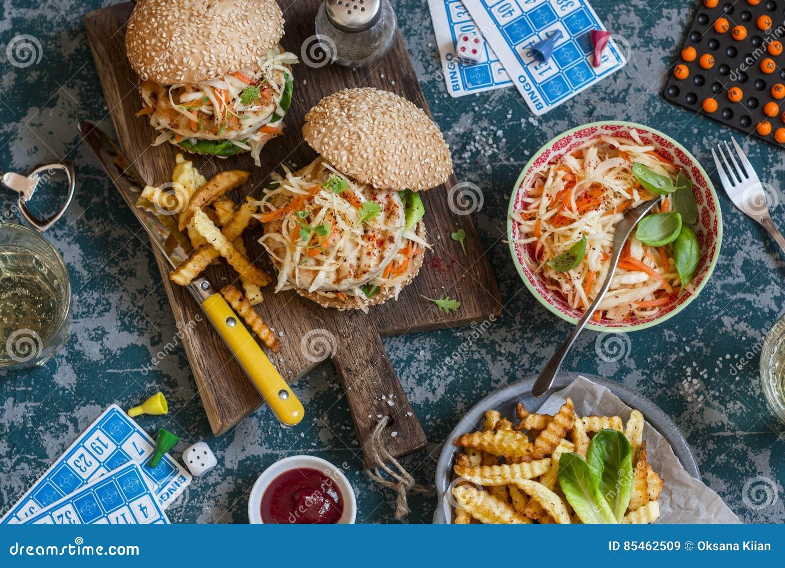 Os Hamburger com slaw grelhado da galinha e do cole em uma placa de madeira na tabela com cartões e bingo lascam-se, vista superi