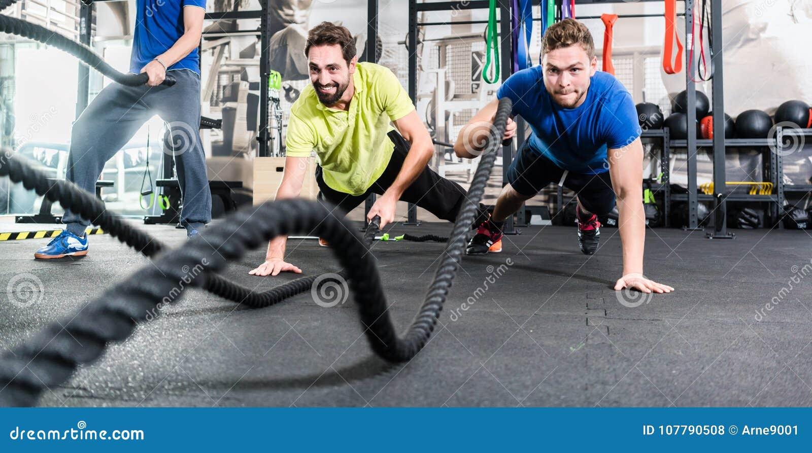 Os homens com batalha rope no gym funcional da aptidão do treinamento