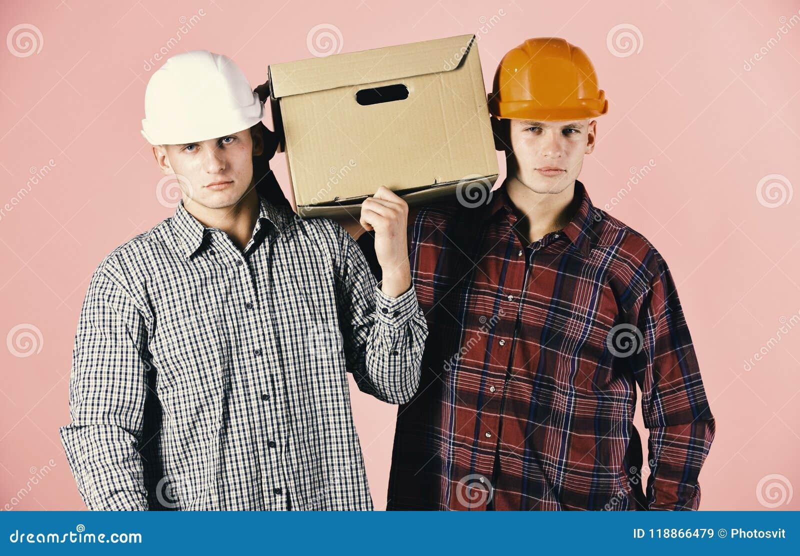 Os homens com caras mal-humoradas guardam a caixa de cartão no fundo cor-de-rosa Entrega, armazém e conceito de empacotamento Irm