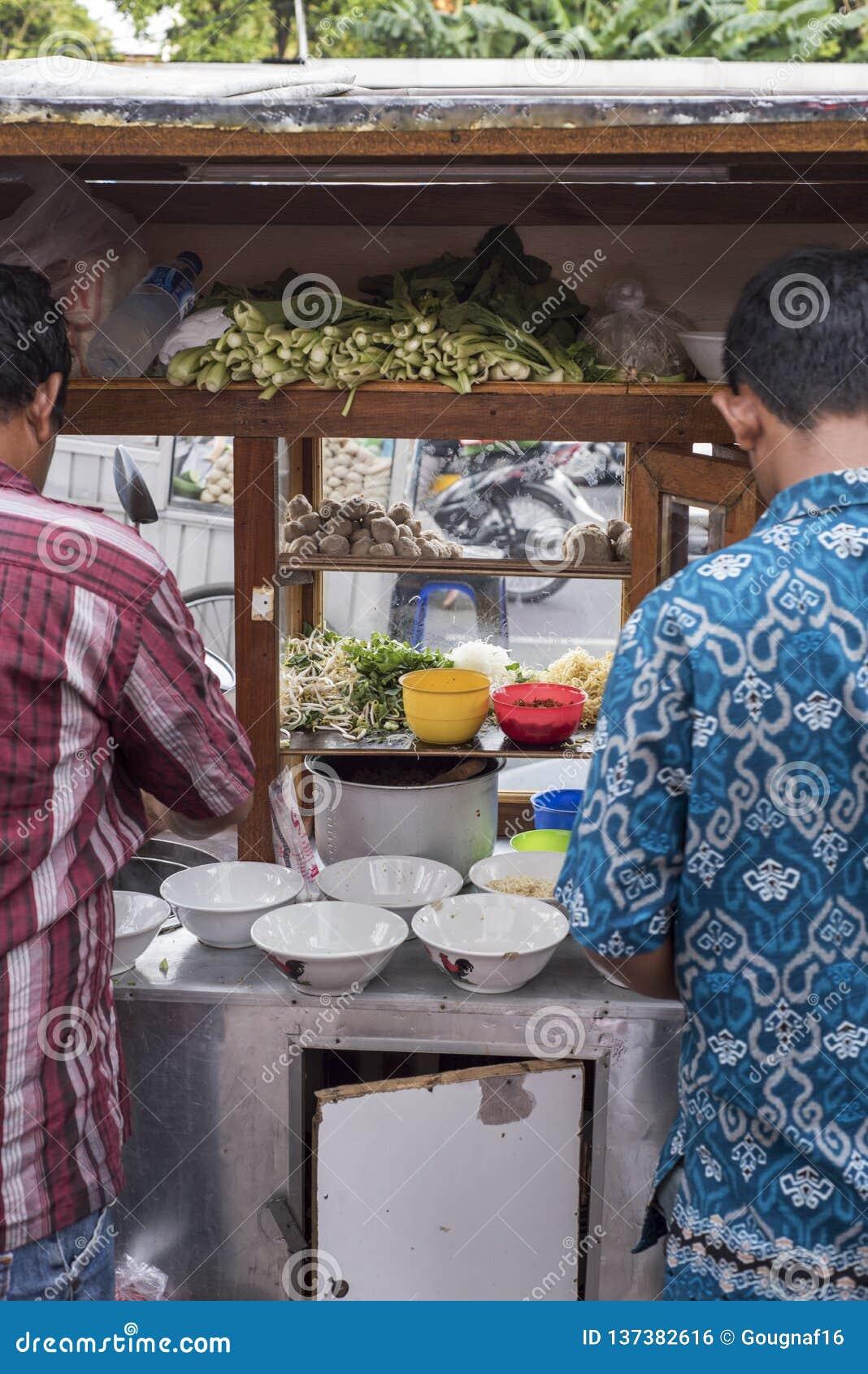 Os homens de Indonésia preparam o alimento em um carro de madeira do impulso do alimento da rua do vintage em Jakarta, Indonésia