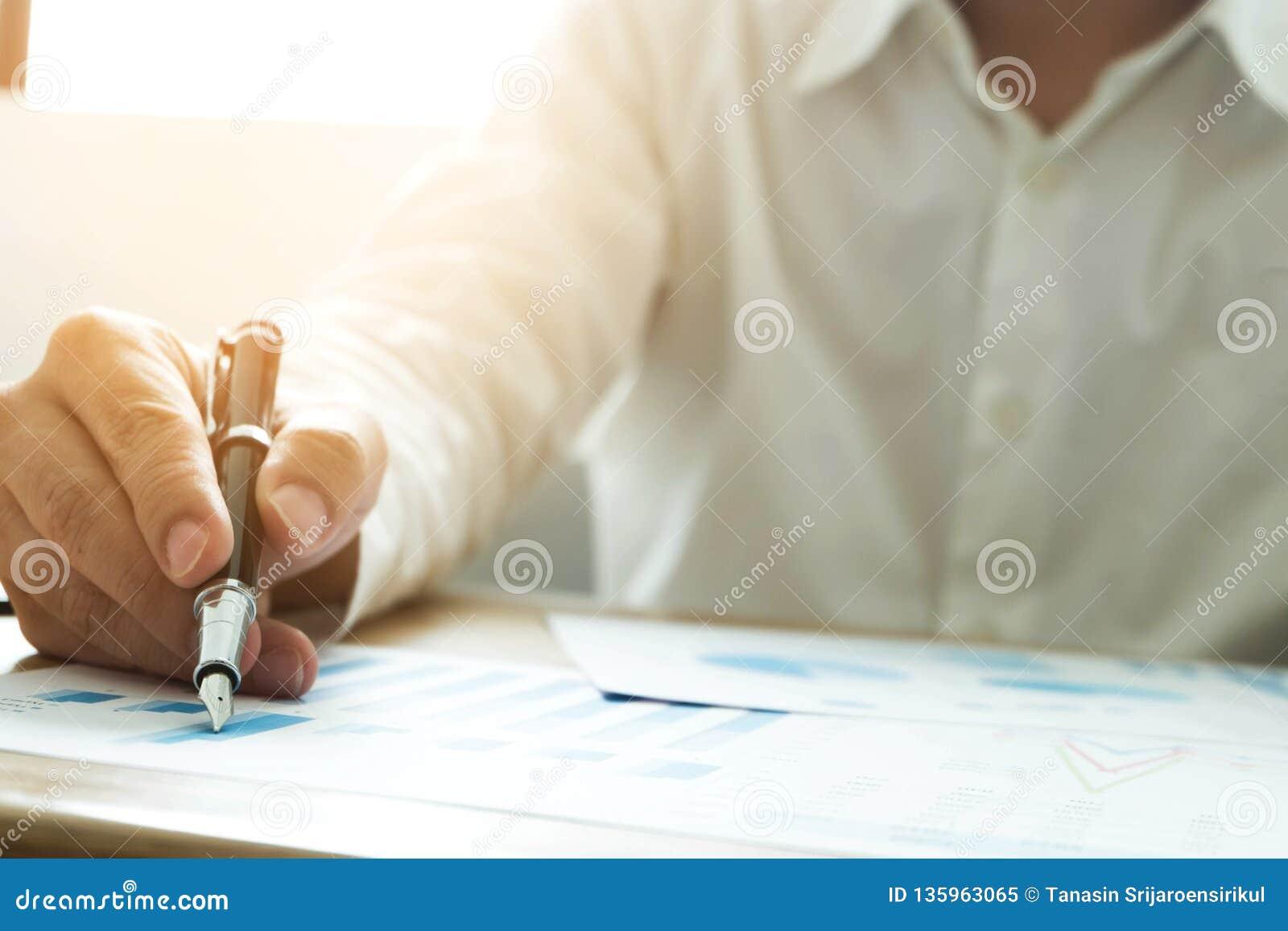 Os homens de negócios estão apontando números, gráfico, carta em resultados de negócio Conceito do negócio