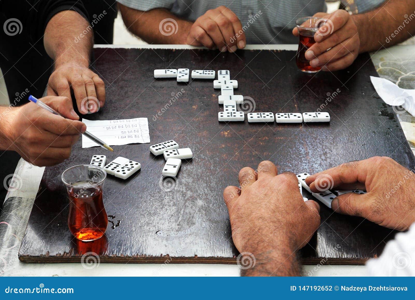 Os homens nos salões de chá bebem dominós do chá e do jogo