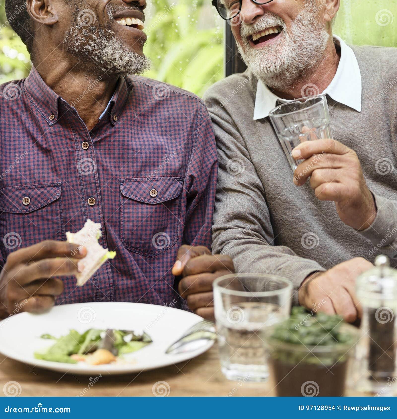Os homens superiores relaxam o estilo de vida que jantam o conceito