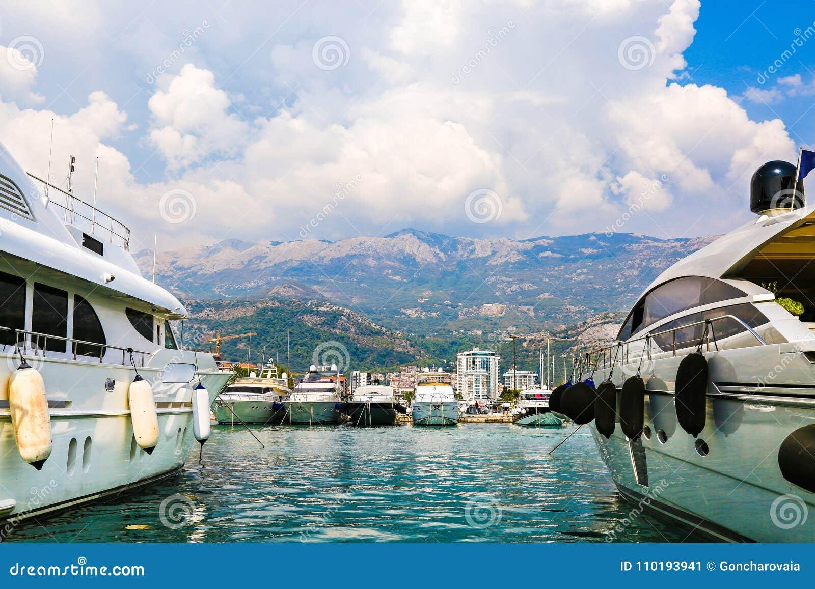 Os iate e os navios de navigação luxuosos amarraram no cais no porto de Budva, Montenegro Porto no mar Barcos e veleiros brancos