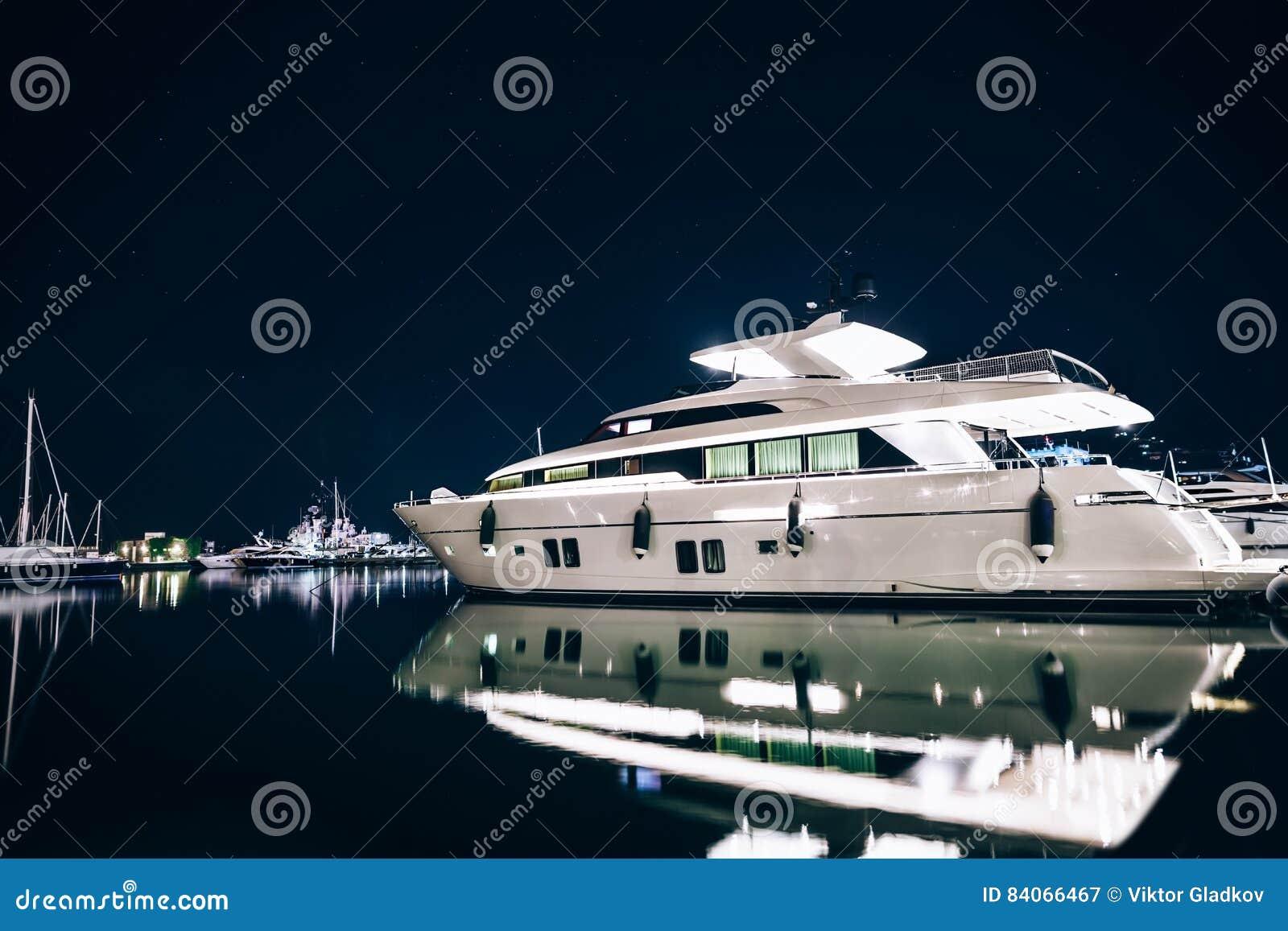 Os iate luxuosos no La Spezia abrigam na noite com reflexão no wa