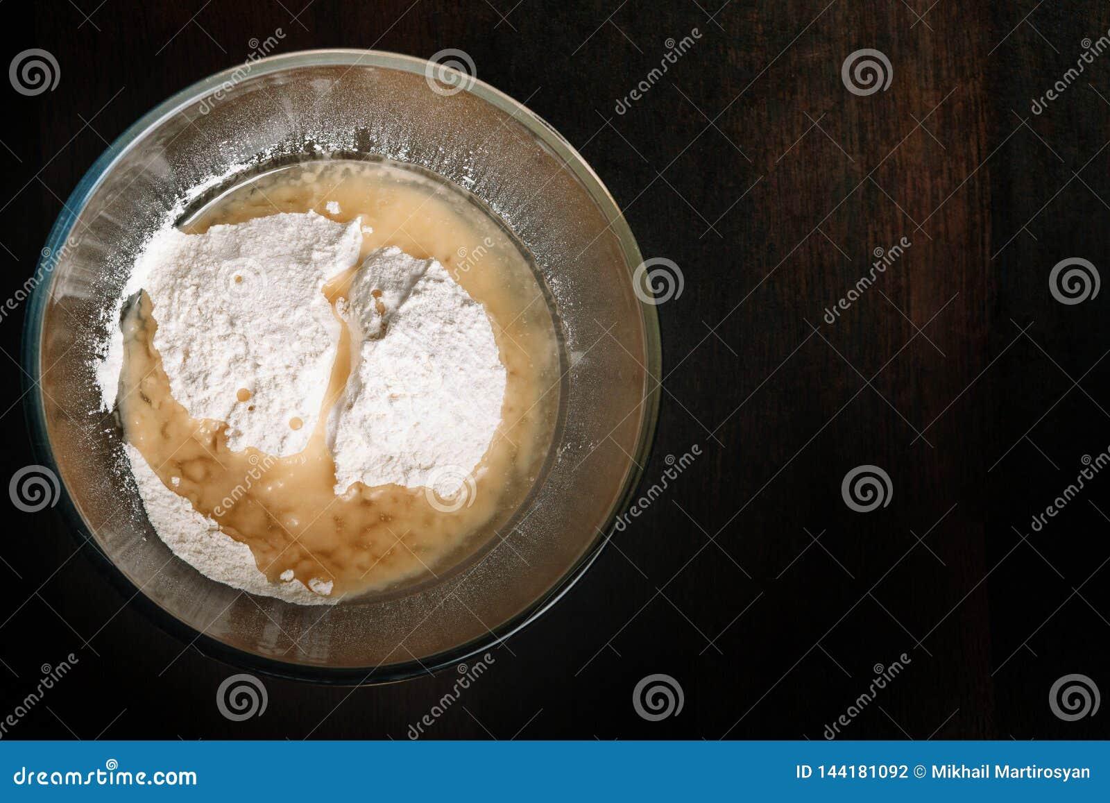 Os ingredientes de cozimento misturaram em uma bacia de vidro Preparação para a massa de amasso