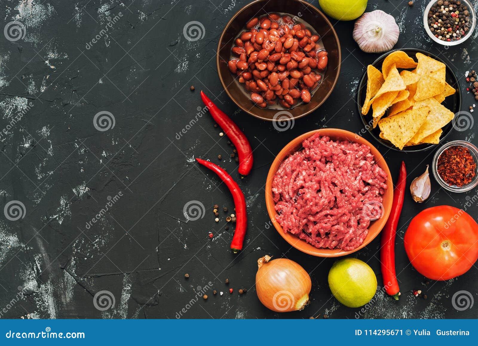 Os ingredientes para o mexicano tornam côncavo chili con carne Fundo concreto preto, vista superior, espaço para o texto