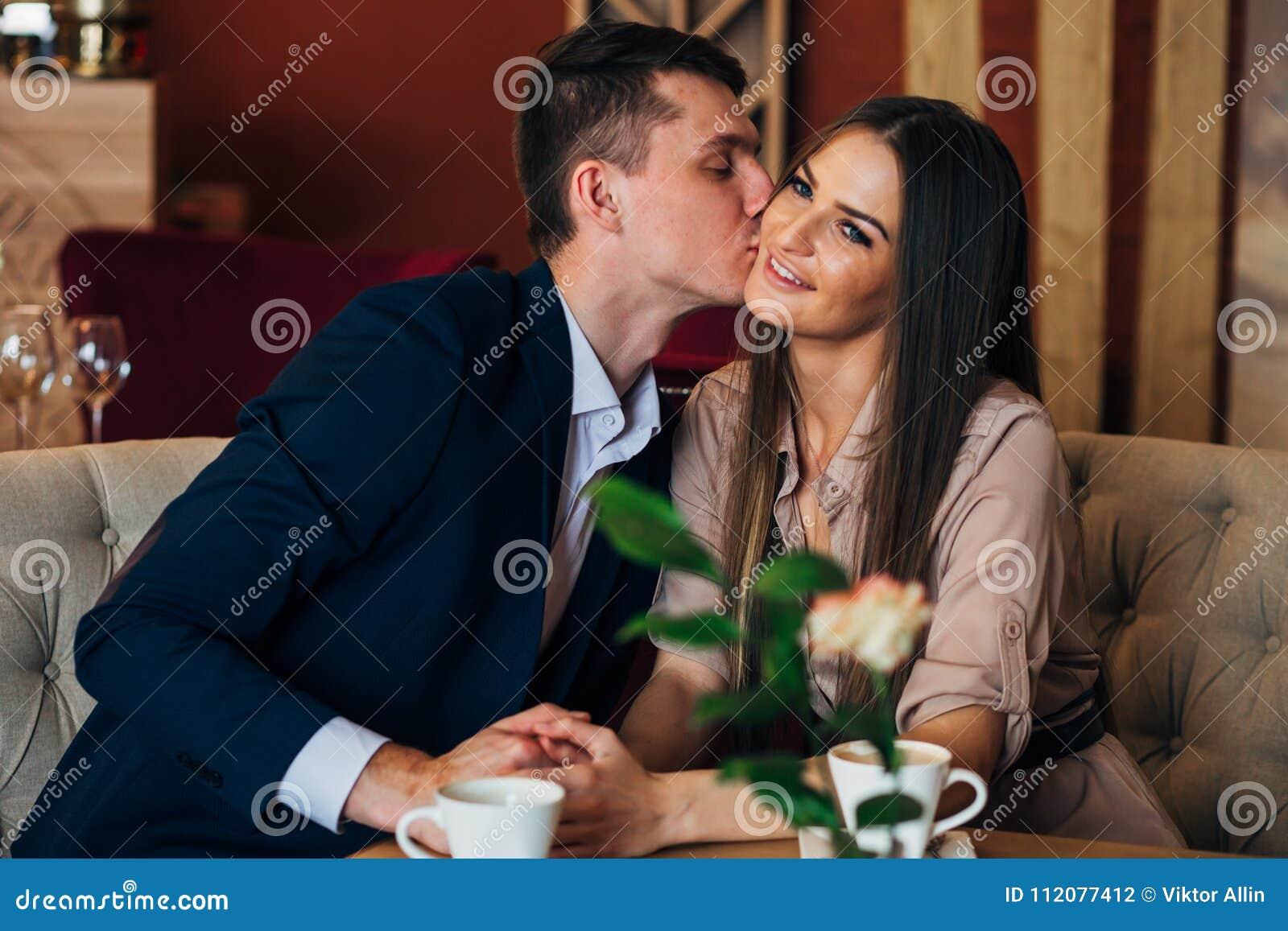 Os jantares de um par em um restaurante um homem beijam uma mulher