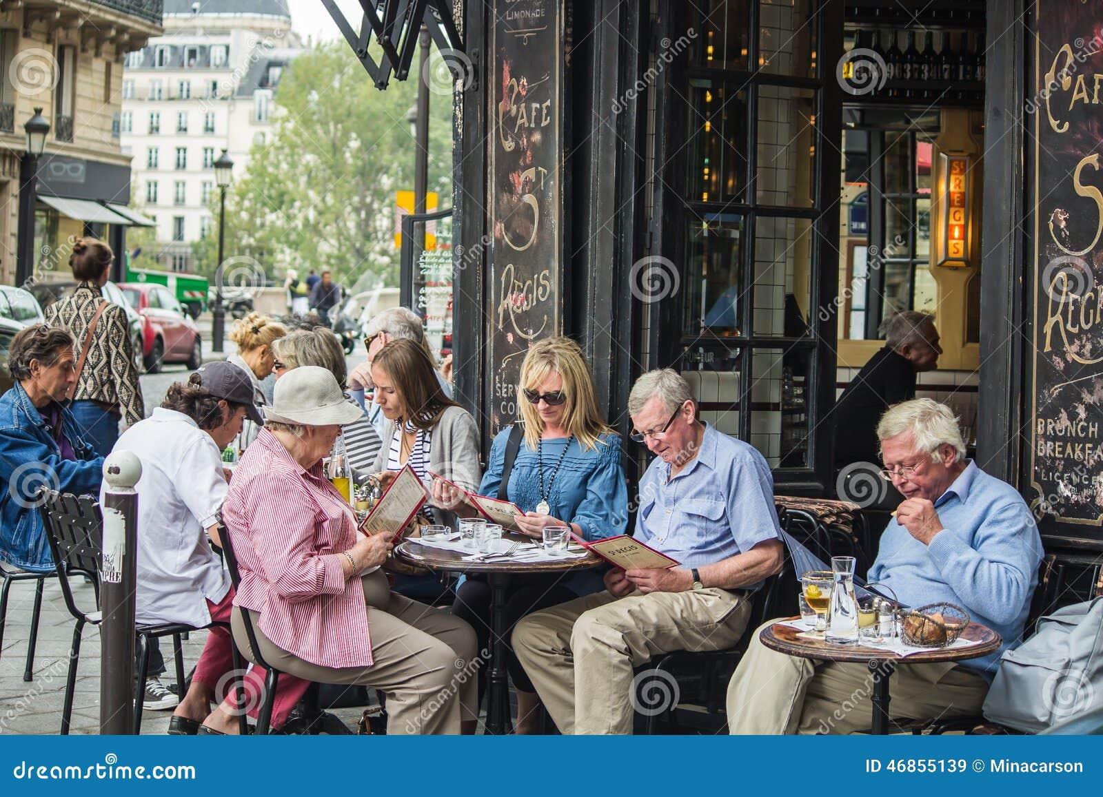 Os jantares estudam os menus no café St Regis em Ile St Louis,