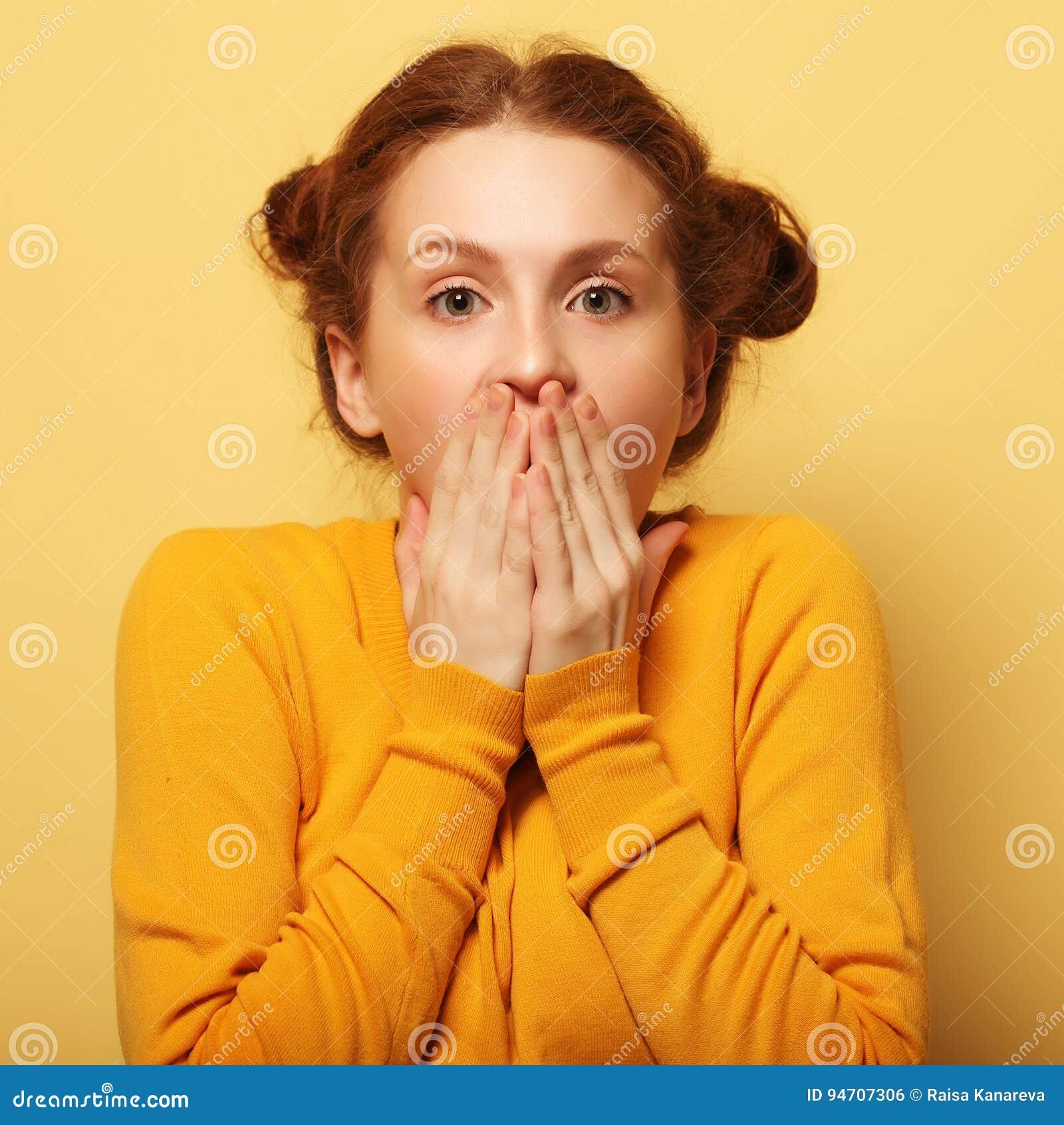 Os jovens bonitos surpreenderam a mulher do redhair sobre o fundo amarelo