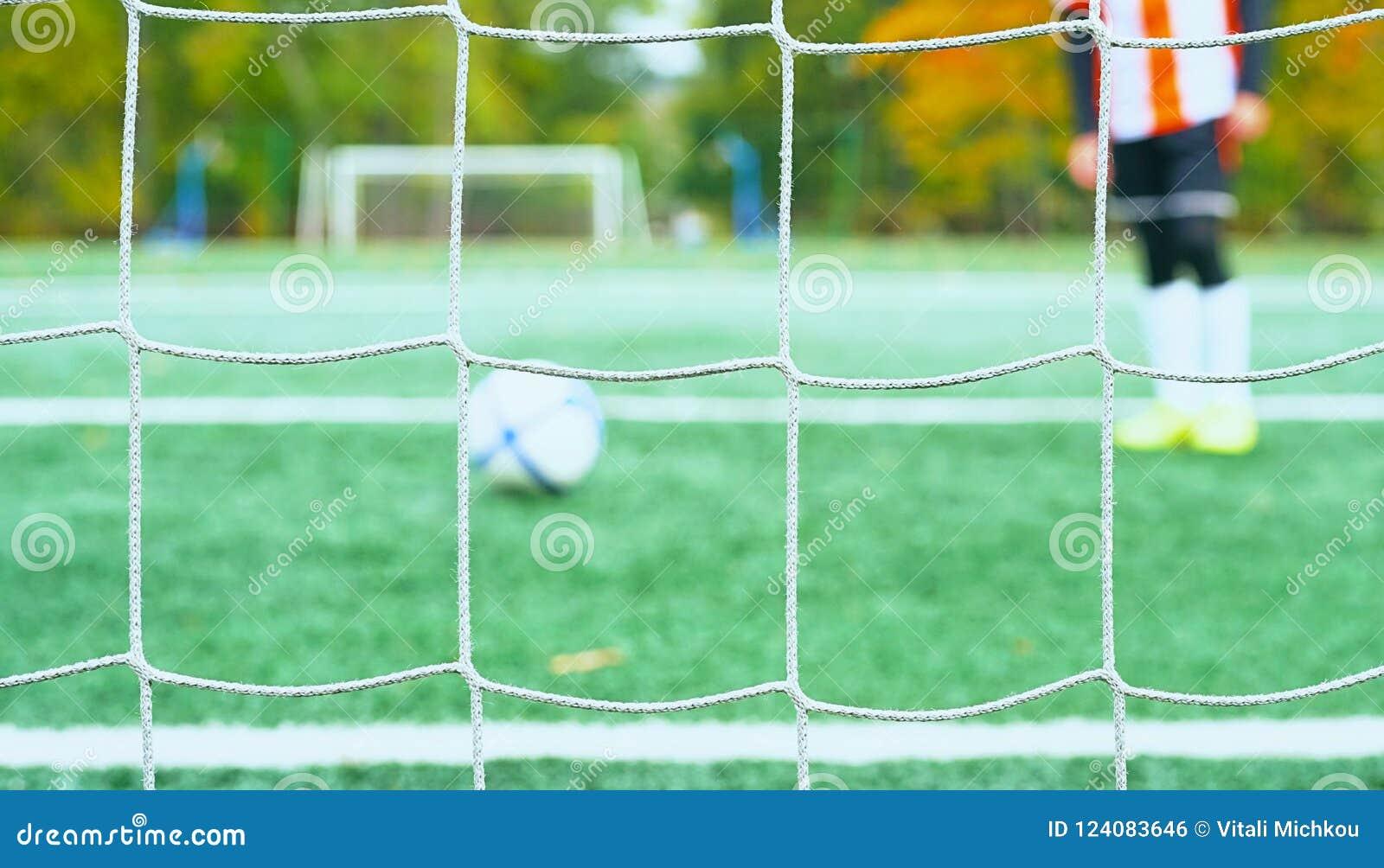 Os jovens borraram o jogador de futebol que toma um pontapé de grande penalidade contra a rede do objetivo