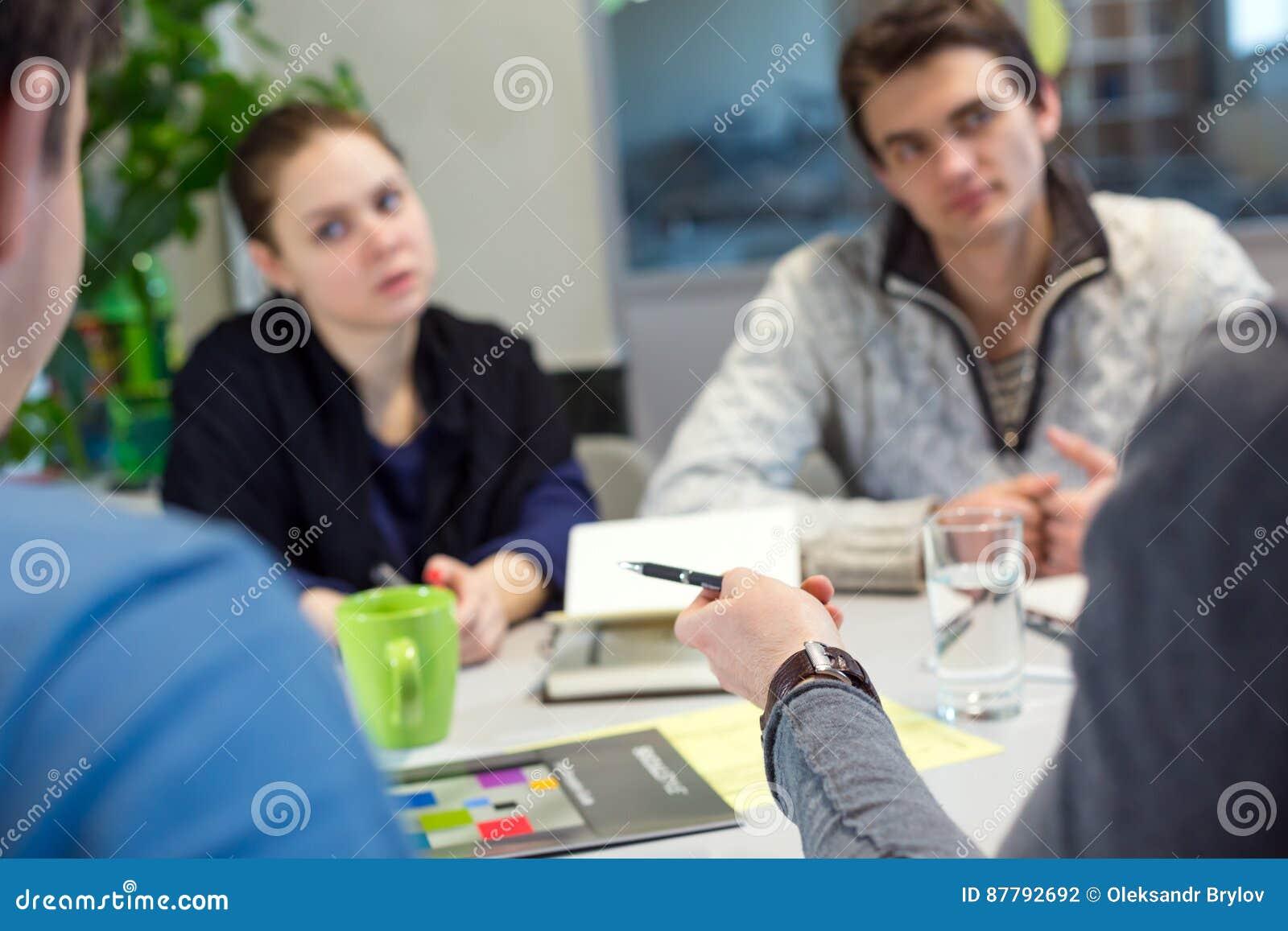 Os jovens da discussão do negócio na roupa ocasional equipam apontar