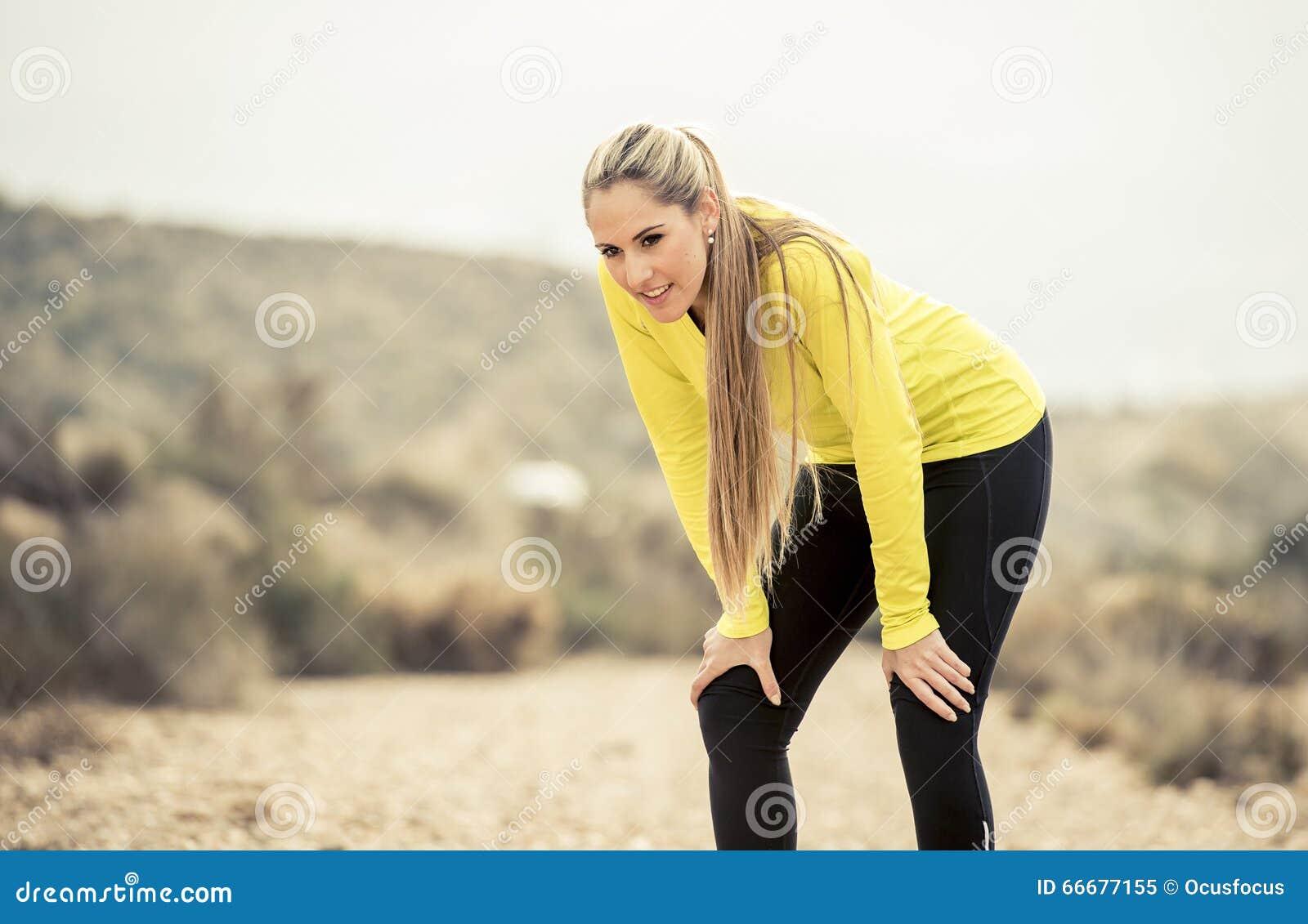 Os jovens esgotaram a mulher do esporte que corre fora na estrada suja que respira