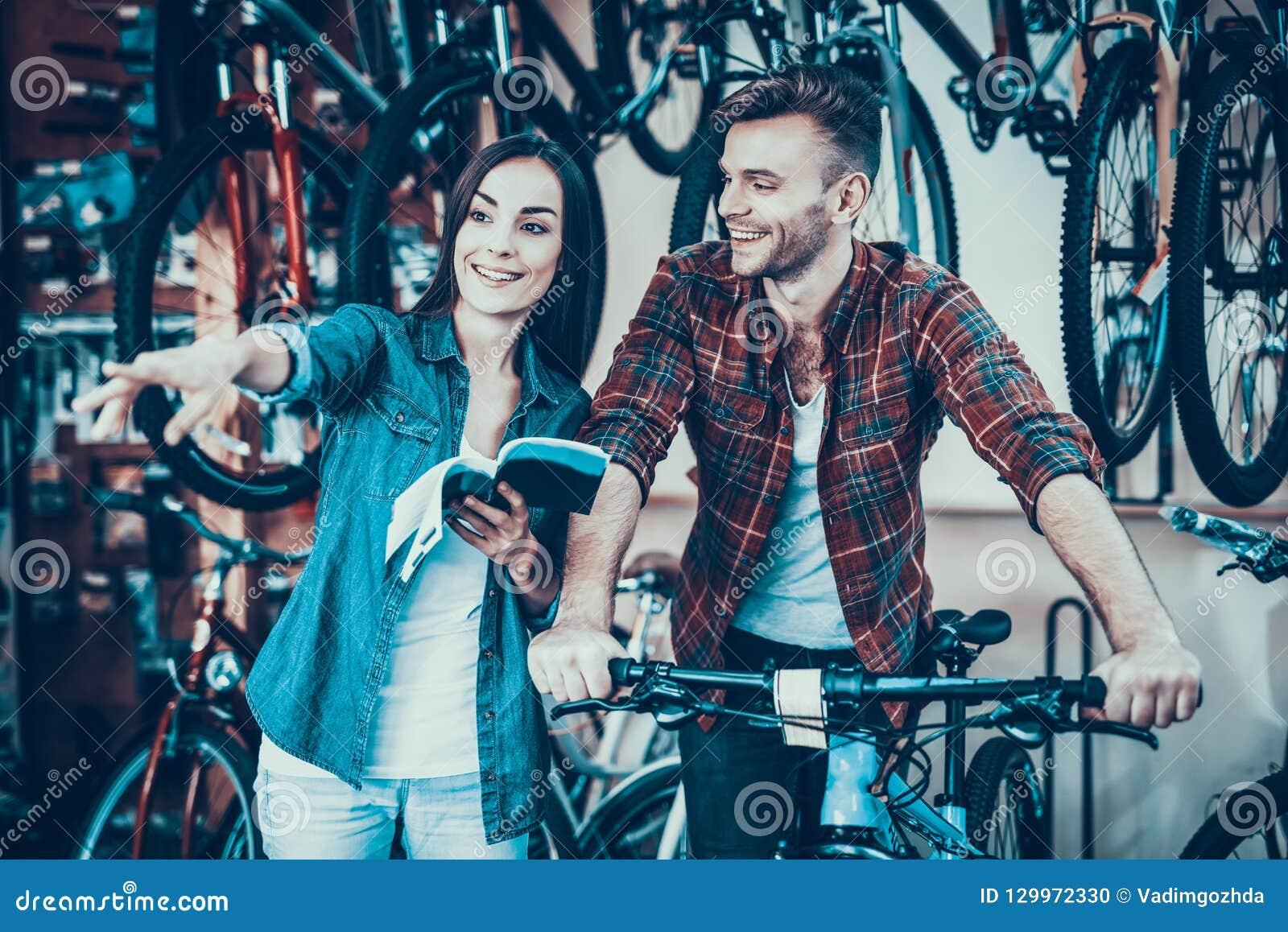 Os jovens felizes acoplam a fala quando escolha a bicicleta nova