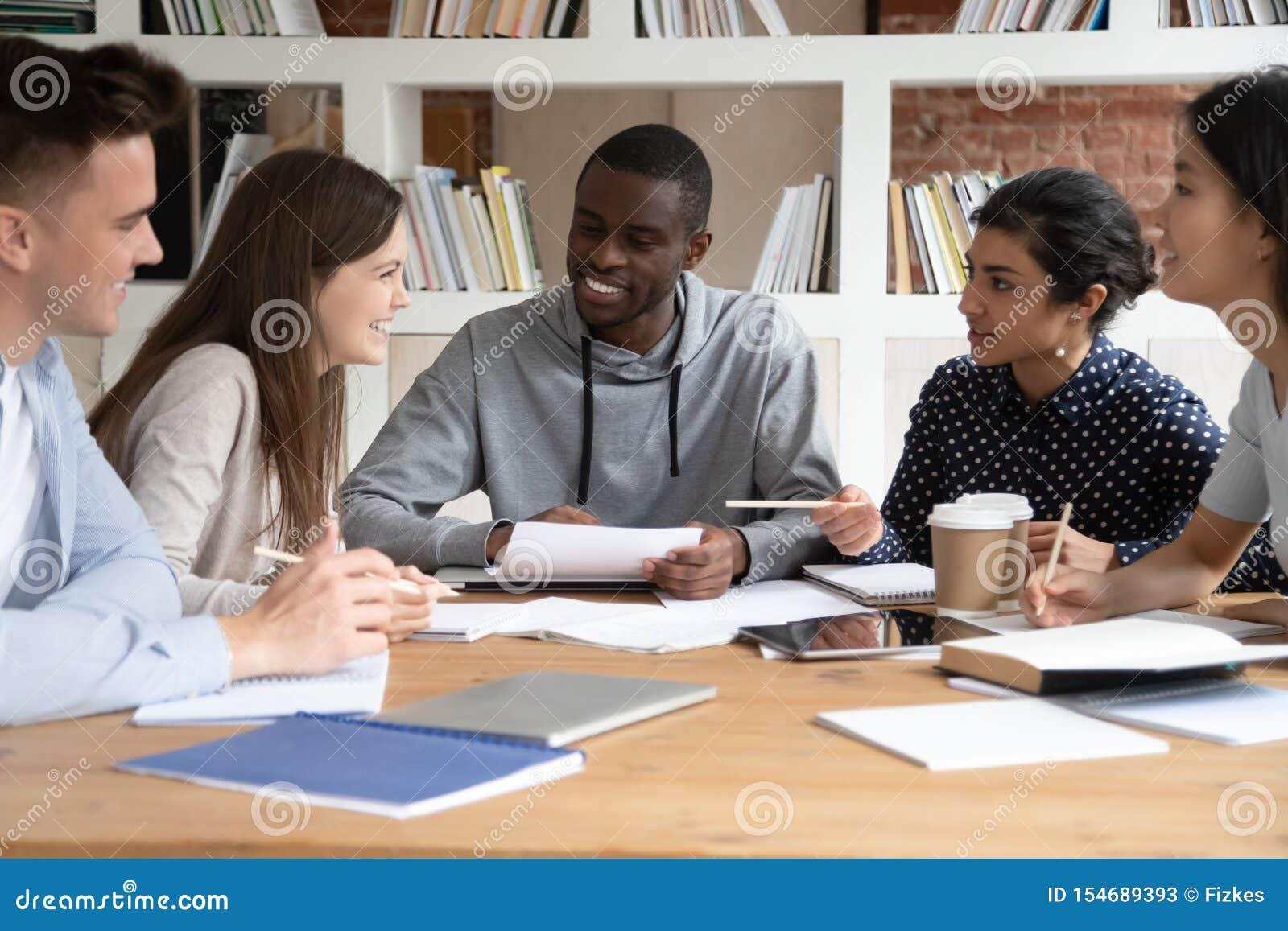 Os jovens multirraciais felizes têm o divertimento que estudam junto