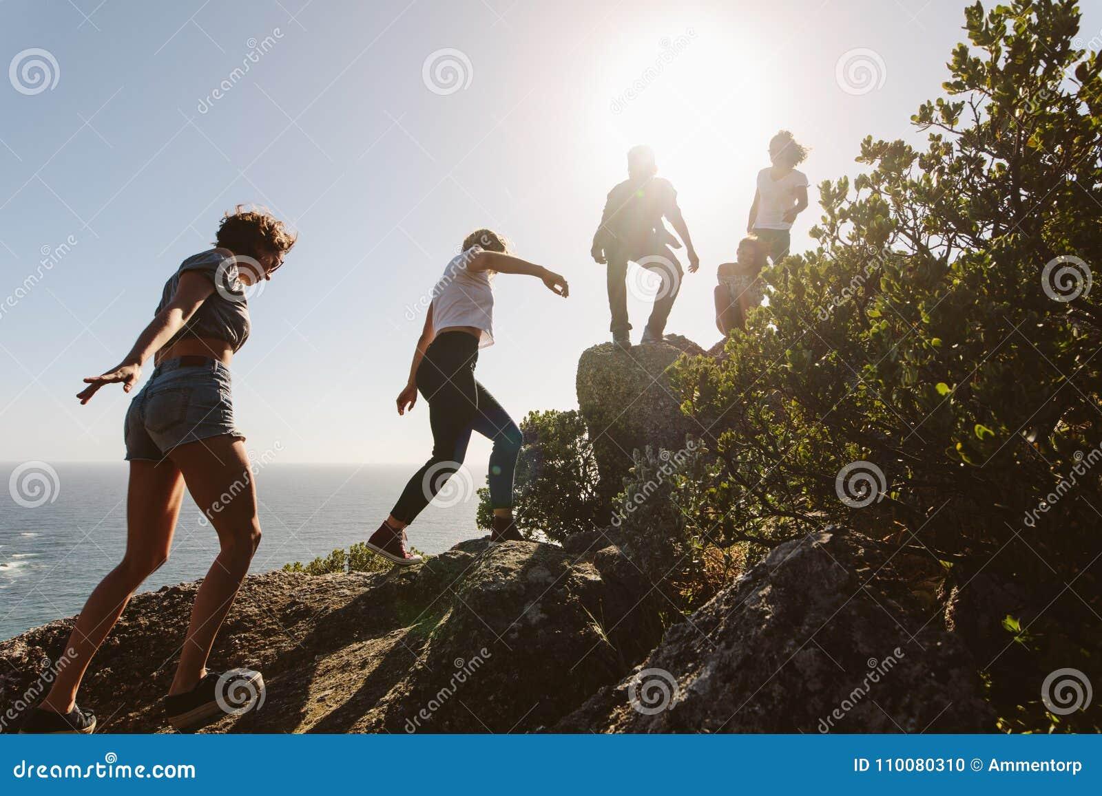 Os jovens na montanha caminham em um dia de verão