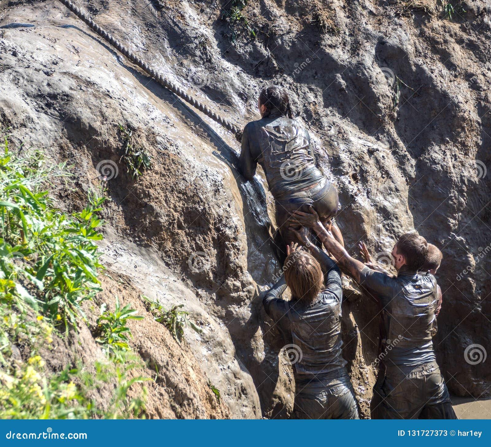Os jovens passam o curso de obstáculo Corredores de raça da lama Escalando a corda teamwork