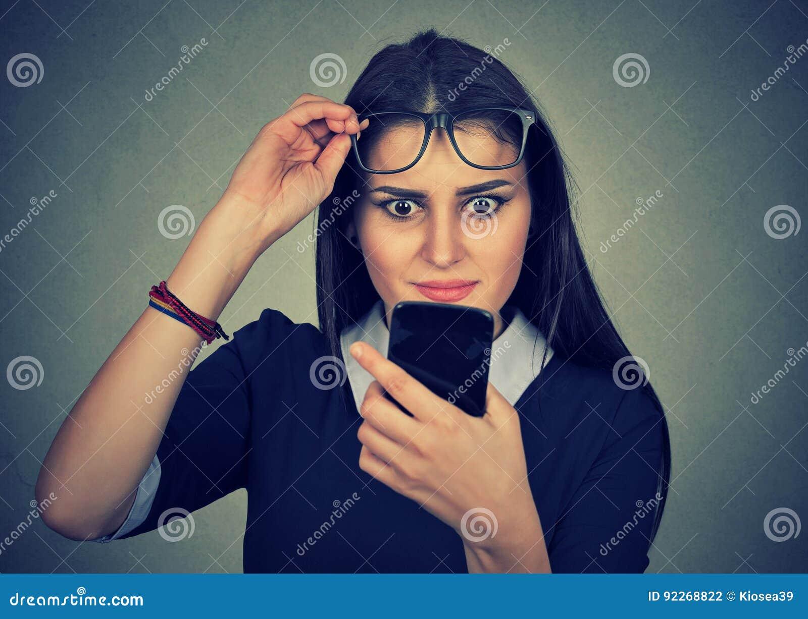 Os jovens viraram mulher confusa com os vidros que olham o telefone celular