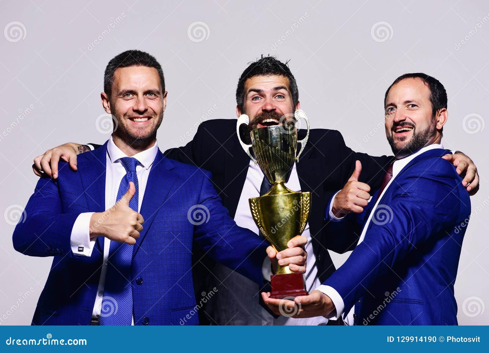 Os líderes da empresa mantêm o prêmio, os polegares da mostra e o abraço dourados