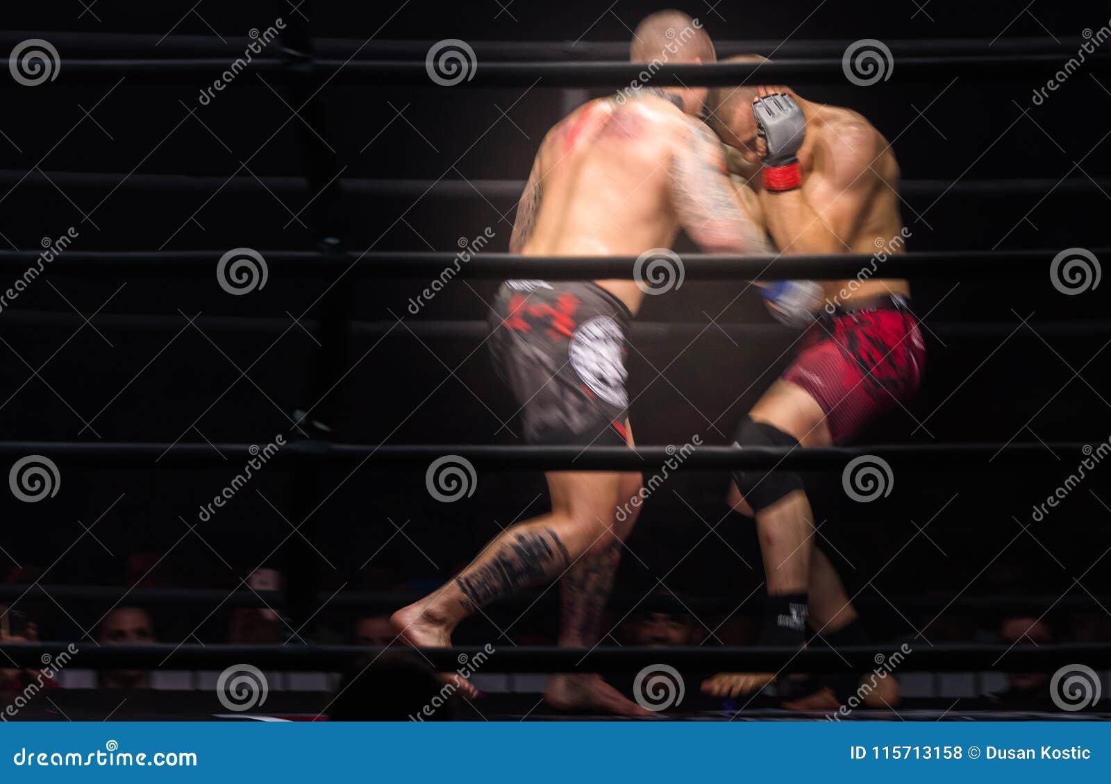 Os lutadores dos pugilistas do Muttahida Majlis-E-Amal lutam nas lutas sem regras no anel