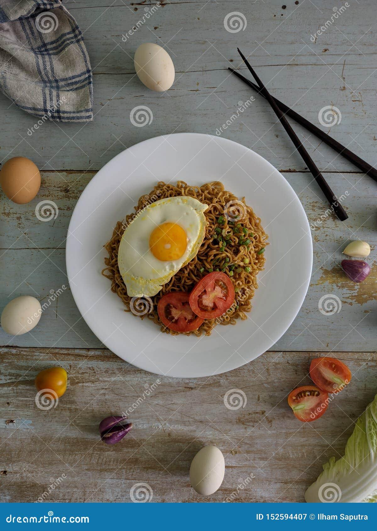 Os macarronetes fritados serviram com ovo frito Conceito colocado liso do alimento Da vista superior no fundo de madeira