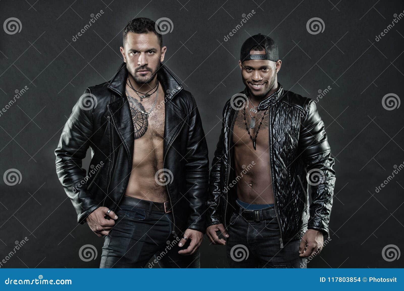 Os Machos com torsos musculares olham atrativos nos casacos de cabedal, fundo escuro Homens nas caras seguras com cerda